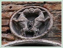 sculpture sur le palais Cappello-Memmo dans le Castello à Venise datant du XIIe siècle et d'un diamètre de 30 centimètres, représente deux chiens dos à dos dont les queues et les gueules sont jointes