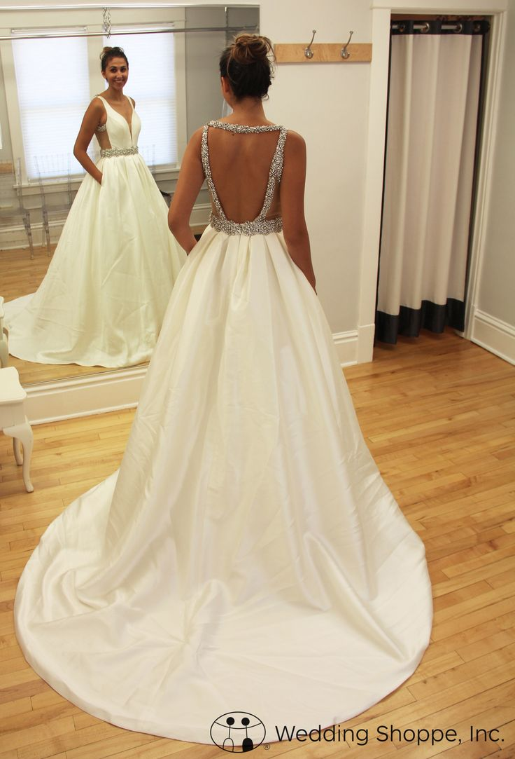 Draped in silky shantung, this dreamy ball gown wedding dress features a fitted sleeveless bodice, a deep V-neckline with an inset sheer panel for subtle coverage, and a stunning open back.