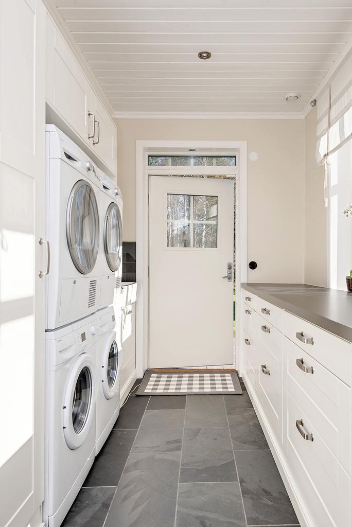 Tvättstuga med dubbla tvättmaskin och torktumlare, gott om arbetsbänkar och förvaring