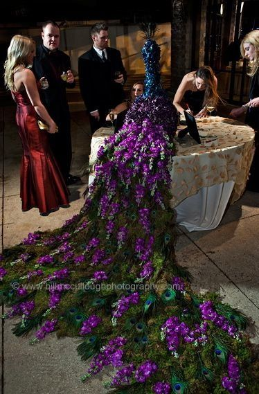 I don't believe this is a Wedding Style image, however it's fabulous.  A peacock made of blue and purple hydrangeas with a cascading tail of fresh moss covered in peacock feathers and purple stock flowers will highlight the guestbook table under the gazebo.