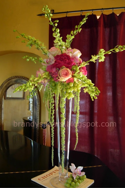Tall wedding centerpiece in pinks of hanging grapes