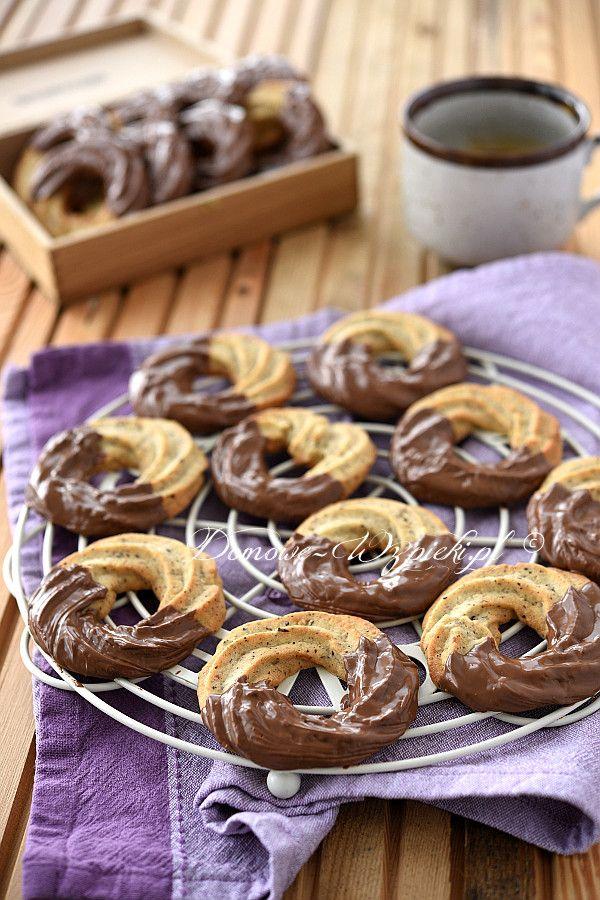 Proste ciastka wyciskane z rękawa cukierniczego, lekko migdałowe i do połowy oblane czekoladą.