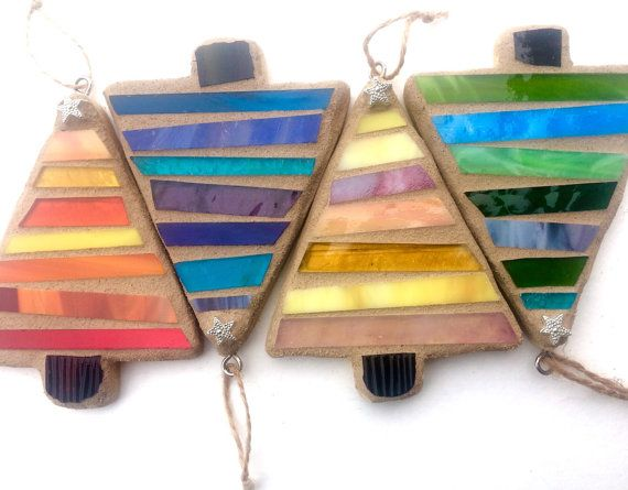 Ready to order! It is never too soon to get started on your Christmas shopping.  These stripe-y trees have a rustic charm along with fun color! Quality farm grown pine wood base, variety of stained glass in your choice of colors. Slightly askew stripes reminiscent of Whoville trees.  Measuring 4.66 in height, 3.5 at widest point, 1/2 thick. Sand colored grout, finished on one side with sealed wood base. Hangs with burlap twine. Topped with silver star!  Order color by picture 2:  1-Red…