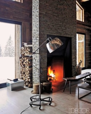 A slate fireplace extends from floor to ceiling in the living room of a chalet in the French Alps. A niche behind the chimney provides storage for logs and kindling; rustic-­chic touches include a vintage dentist's lamp and a weathered farm bench.