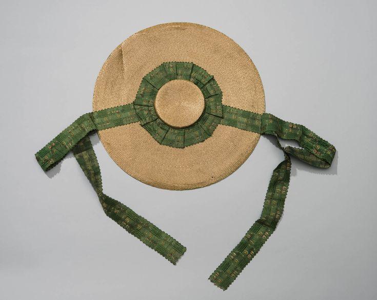 Zogenaamde schelphoed, tegengevoerd met Indiase sits of Europese katoendruk met 'pilaer'dessin op blauwfond. Rond de bol heeft de hoed een garnering van groen lint. vermoedelijk Axel, voor ca 1850 #Axel