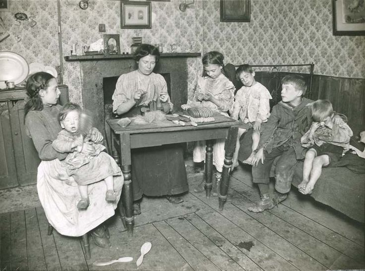 A family making hairbrushes at home in the East End, c. 1900.