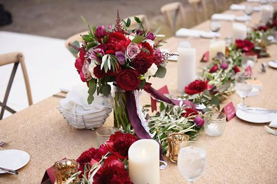 Wedding tablescape: gold brocade tablecloths, a mix of pillar candles and votives with roses and greens running down the center. Red, White, and Rosy Real Wedding at Atlanta History Center // Susan Graham Signature Events | Laura Stone Photography