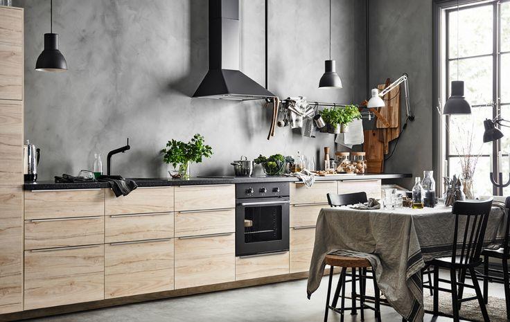 Einzeilige Küche mit einer Reihe von Unterschränken, die Eschentüren haben. Dahinter eine graue, betonartige Wand sowie ein Esstisch mit Leinentischdecke