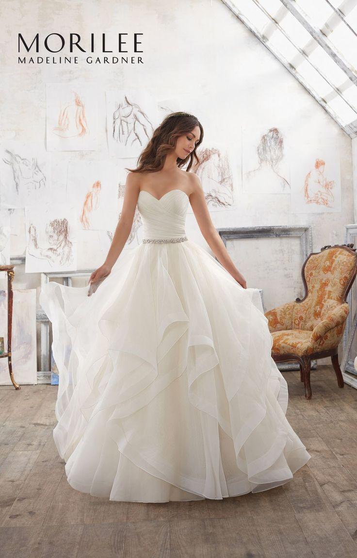 Drapowany gorset w kształcie serca i dziewczęce falbany sukni ślubnej Mori Lee. Efektowna, warstwowa spódnica z organzy, lekkie falbany. Asymetrycznie …