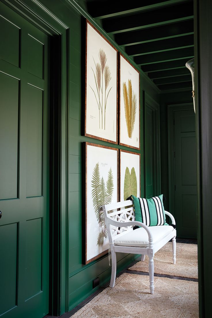 Bill Ingram's green hallway in the 2016 Southern Living Idea House, emerald green walls with large grid arrangement of art of flora
