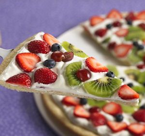 Uses sugar cookie dough spread in a pan in a thin layer and baked. Then mix cream cheese (the normal block size, 8oz) with about a1/3 cup of granulated sugar which is spread over the cookie once cooled. This is topped with fresh fruit sliced, usually strawberries. Sometimes kiwi or blueberries or other fruit, depending what is in season.