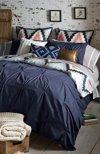 Would probably do some shade of gray on the wall (don't really care for white washed floors or brick in a bedroom). Maybe have a thick wooden headboard with mason jar or lantern lights, and a trunk at the end of the bed. Love this bedset though - M.