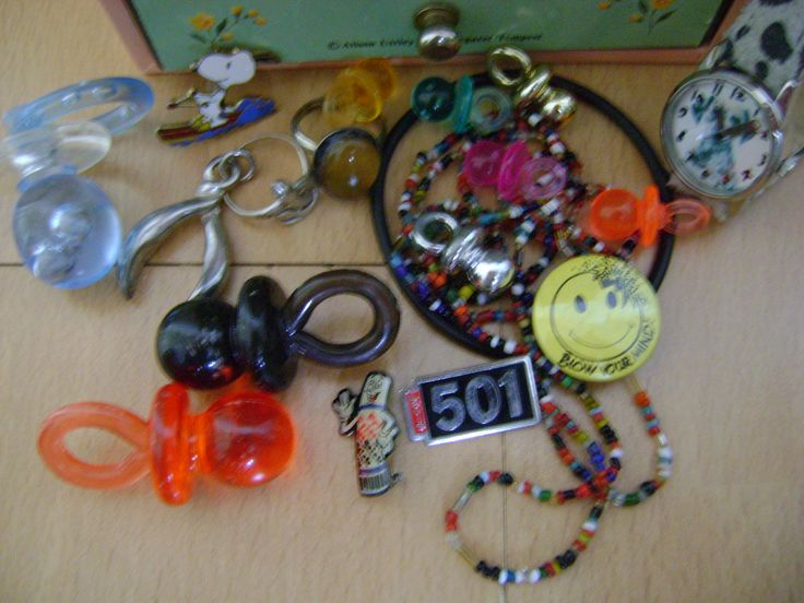 90s jewellery - love beads, dummies, mood ring, pins and acid badge.