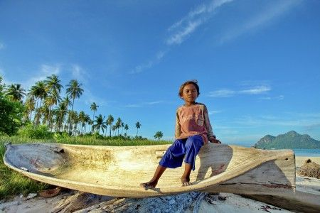 Muslianshah Bin Masrie: Captured at the beautiful Maiga Island, Malaysia. The young sea gypsy boy sitting at the wooden boat belongs to his father.