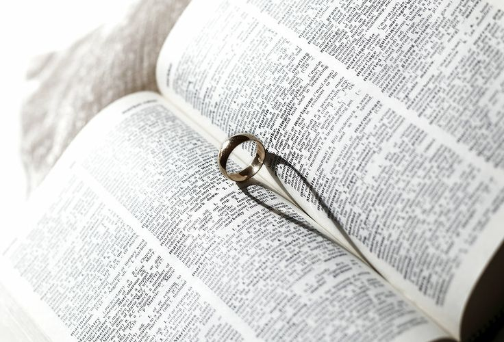 Love & Marriage - wedding ring on an open book next to definition of Marriage.  Light source creates a heart shaped shadow.