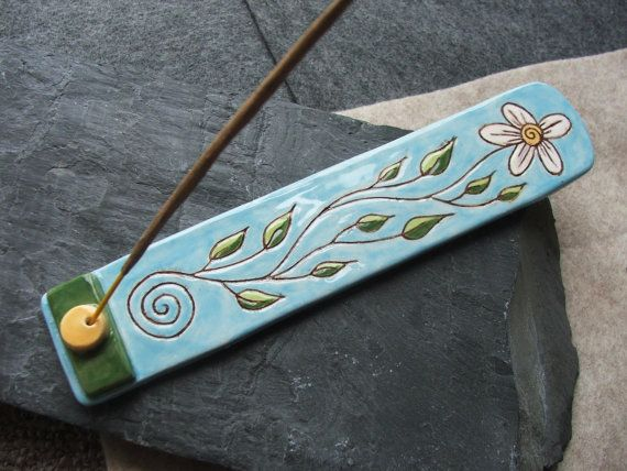 This ceramic incense holder was made from earthenware clay before carving in a summery design of a leafy white flower flowing up from a spiral.  The piece was fired to 1000C. After firing I applied vibrant non-toxic glazes to the upper surface and fired again to 1120C.  The base is unglazed.  This incense holder will happily take most stick incense.   The piece measures approximately 19cm long and 4cm wide.  https://www.etsy.com/uk/listing/191531351/handmade-ceramic-spiral-flower-leaf