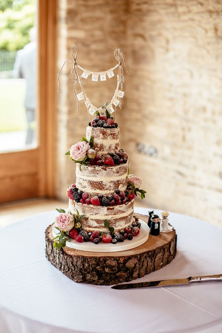 Three tier naked wedding cake decorated with fresh fruit and flowers. Photography by Cassandra Lane.