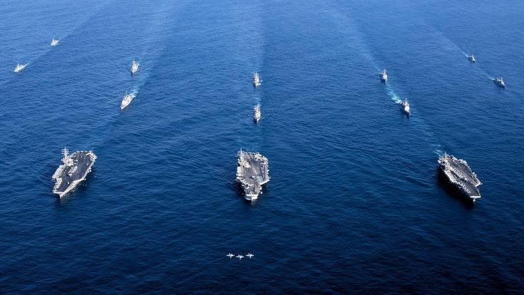 The USS Ronald Reagan, USS Theodore Roosevelt, and USS Nimitz Strike groups sail together in the Western Pacific within international waters as part of a three-carrier strike force exercise demonstrating the U.S. Navy's unique capability to operate multiple carrier strike groups.