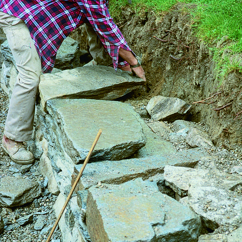 Build a Dry-Stacked Stone Retaining Wall - Fine Gardening - Learn how to build your own stone wall to retain and divide areas of your yard.