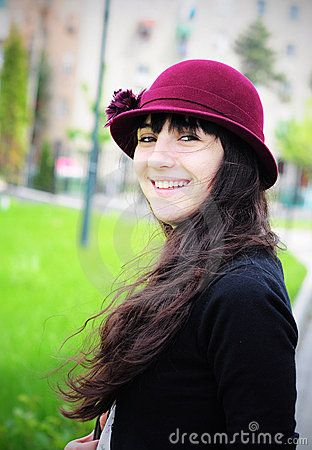 Portrait of an elegant young woman, wearing hat, smiling in the park