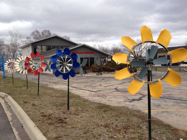 Windflower kinetic garden sculptures made from recycled bicycle rims, plumbing parts, PVC foam sheets and garden stakes. Made at WindworkerStudio.com, Madison, WI