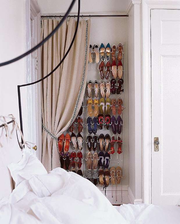 Turn a shallow alcove into a shoe closet by attaching a shoe rack to the wall and hanging a curtain. - Domino / Steven Randazzo