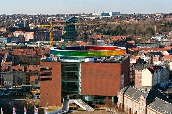 Радужная инсталляция на крыше здания от Олафура Элиассона. На крыше одного из самых высоких зданий в датском городе Орхус вот уже несколько лет существует необычная конструкция в виде радужной окружности, полностью опоясывающей верхнюю точку этого строения. Создал инсталляцию известный датско-исландский художник Олафур Элиассон (Olafur Eliasson), который известен на весь мир своими экспериментами со светом, цветом и пространством.