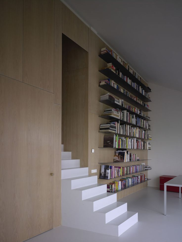I like the way this simple white stair pops out from the wood panelled wall. The shelves finish the look for me.