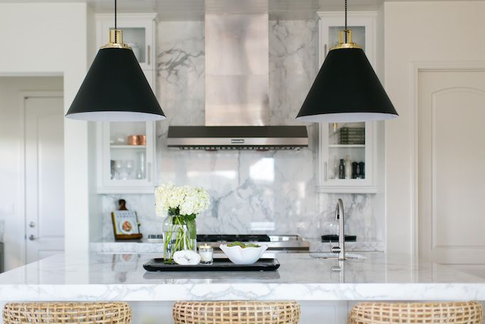 BECKI OWENS- Estillo Project: Classic Modern Kitchen. A white kitchen  with statuary marble, Benjamin Moore Swiss Coffee paint, black cone pendants, rattan counter stools, island prep sink, and stainless steel apron sink.