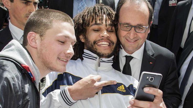 Un jeune homme fait un selfie et un doigt d'honneur avec François Hollande à Berne (Suisse), le 15 avril 2015. | THOMAS HODEL / AP / SIPA
