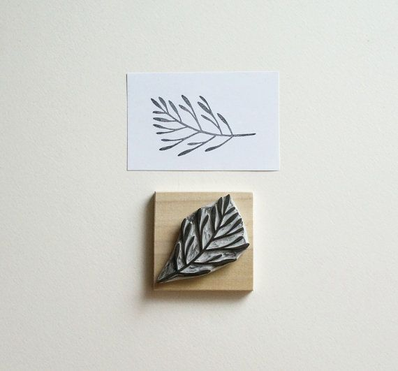 A large floral branch stamp hand-carved out of rubber.  The stamp is mounted on a piece of sanded wood. It comes in a recycled plastic and cardboard