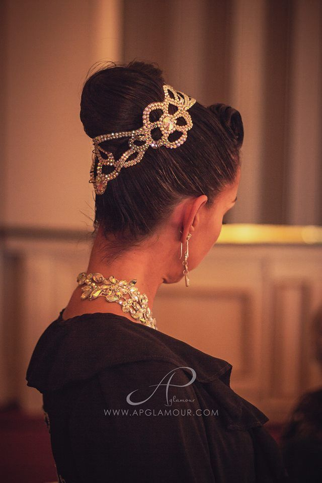 High bun wrapped with a stoned hairpiece and upwards bang swoop. Visit http://ballroomguide.com/comp/hair_make_up.html for more hair and makeup info