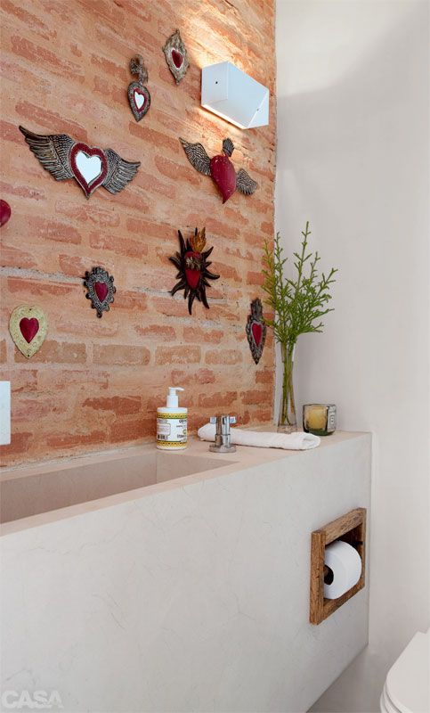 """Mix de rústico e moderno - """"Esta parede de tijolos aparentes prolonga-se da sala de estar para o lavabo e, nos dois ambientes, expõe obras de arte"""", diz a arquiteta Kika Camasmie, autora do projeto de reforma do lavabo de 1,30 m x 95 cm. A ideia de integração visual aparece ainda em detalhes, como a papeleira de madeira de demolição, material usado em todas as portas do apartamento. A bancada é de mármore crema marfil jateado. Luminária da La Lampe."""