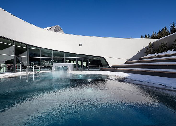 This alpine aquatic centre by Auer Weber has wide crescent-shaped windows overlooking the piste at the popular ski resort of Courchevel