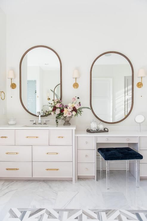 Oval wood framed mirrors flanked by Camille Long Sconces are hung above a light gray dresser washstand and makeup vanity.