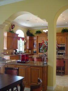 Diese toskanischen inspirierte Küche mit Bögen Funktionen Granit, erhöhte Panel Schränke, mittlerer Ton Schränke und Geräte aus rostfreiem Stahl. Die Bögen, dient als Eingangsbereich und das halten der Küchenbar mit braunen Holz Schränke und Granit Counterpost, brechen die Küche mit Essbereich. Mehrere Betriebsdekorationen sind ebenfalls bemerkenswert. Foto von RAFAEL DAVILA durchsuchen Mittelmeer Küche Ideen