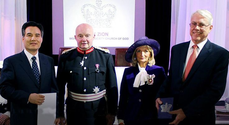 Pastor Kim Joo-cheol (left) received the award certificate signed by the Queen and the commemorative crystal of the Queen's Award from the Lord Lieutenant of Greater Manchester, Warren Smith (second from left),