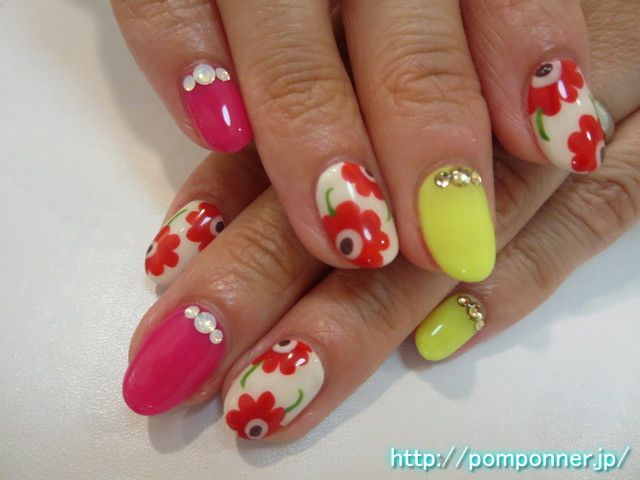 蛍光カラー×マリメッコが派手可愛なネイル  Fluorescent color × Marimekko is nail Na cute flashy. The monochromatic painted with fluorescent colors, embellished with a stone base. Claws of Marimekko, drew a large handle to the off-white base.