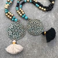 Striking handmade pendant necklace suspending a wonderful Mandala in gold and turquoise on a long strand of alternating coloured beads.   Available in two amazing colours:   - Smooth cream - mixed beads of cream, gold and turquoise - Crisp black - beads mixing gold, turquoise and black