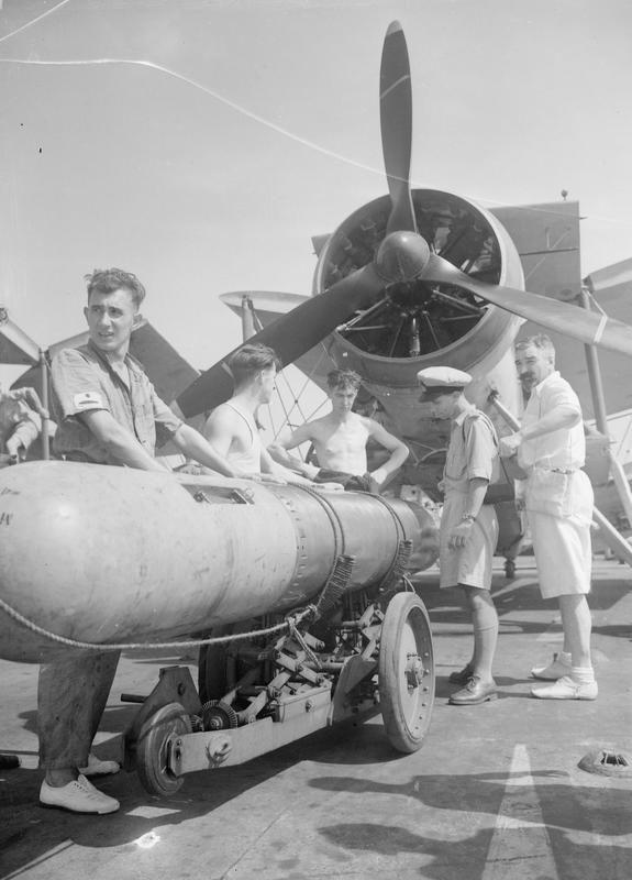 PREPARING FAIREY SWORDFISH FOR TORPEDO DROPPING EXERCISES. HMS ILLUSTRIOUS, 20 OCTOBER 1942./ A torpedo being wheeled into positon under a Fairey Swordfish torpedo-bomber. © IWM (A 12873)