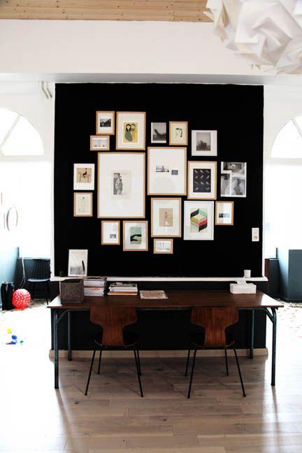 Un coin bureau aménagé derrière un mur sombre (avec une mosaïque de cadres bien serrée) avec 2 chaises fourmi qui jouent la discrétion.