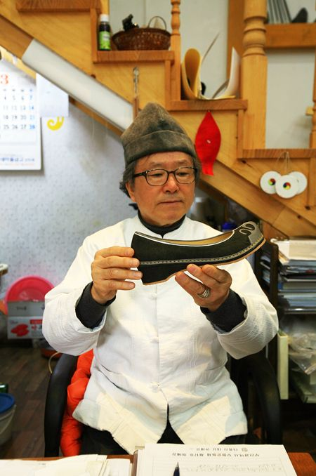 Traditional leather shoe master Ahn Hae-pyo holding a shoe at his workshop in Gamcheon Culture Village in Busan.