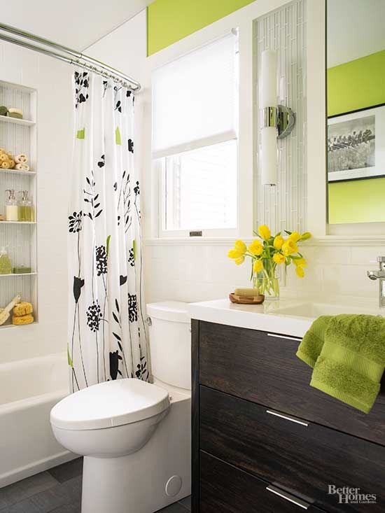 A mix of tile materials, including subway, glass, and bluestone-look porcelain, joins bold green wall paint to create visual interest in this tiny bathroom. The splash of citron, a neonlike hue with yellow undertones, energizes the otherwise monochromatic space./