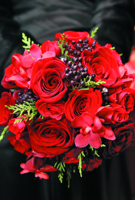 Brides.com: Winter Wedding Flowers. Wedding bouquet of roses, orchids, berries, and greenery by Winston Flowers  Browse more red wedding bouquets.