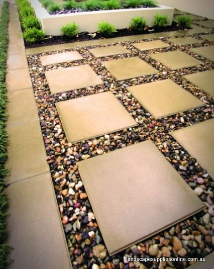 coloured pebbles are used to great effect in between large format pavers do this to extend the tiny patio area into the grassy lawn front and back less