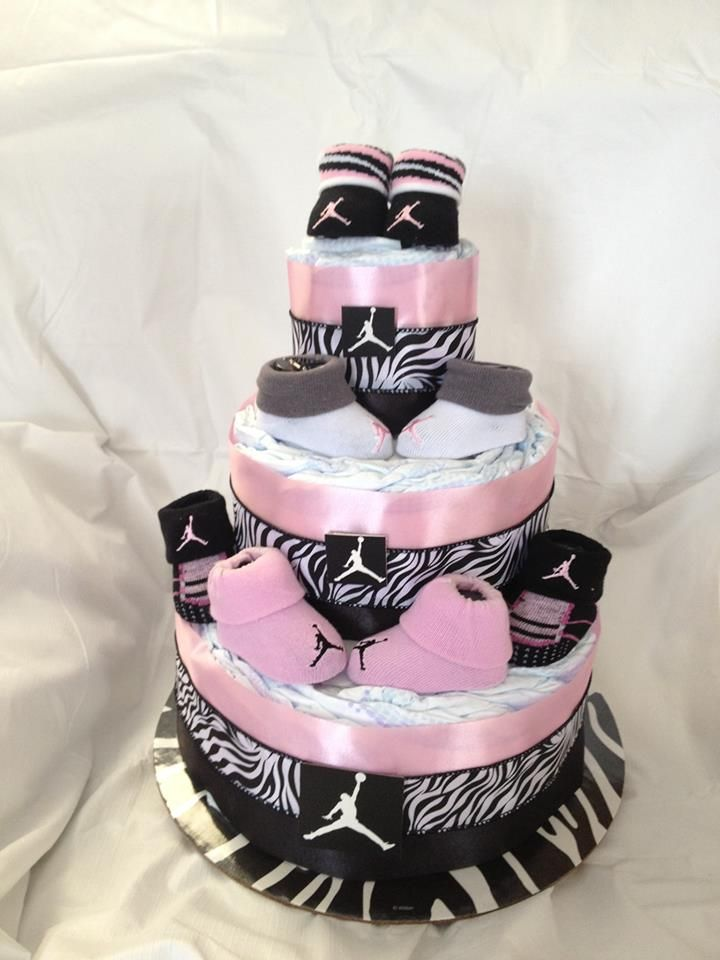 This is a girl themes pamper/ Diaper cake. It is made with receiving blankets, size 1 diaper and Michael Jordan Babies booties. Also available in other colors and themes