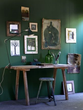 The emerald green in this room acts as as a counterfoil to the artfully arranged artworks which have an organic, loosely assembled feel. This tonality is further extended to the timber of the simply constructed sideboard stool. The enamel lamp in green and the glass bottle draw the eye linking the background and foreground. Photograph by Louis Lemaire - through remodelista
