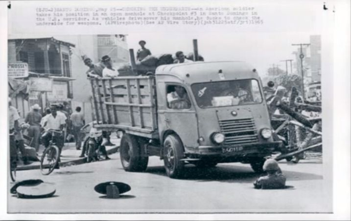 US soldier coming out of a manhole used by the rebels at the same time a truck drive in front of him.