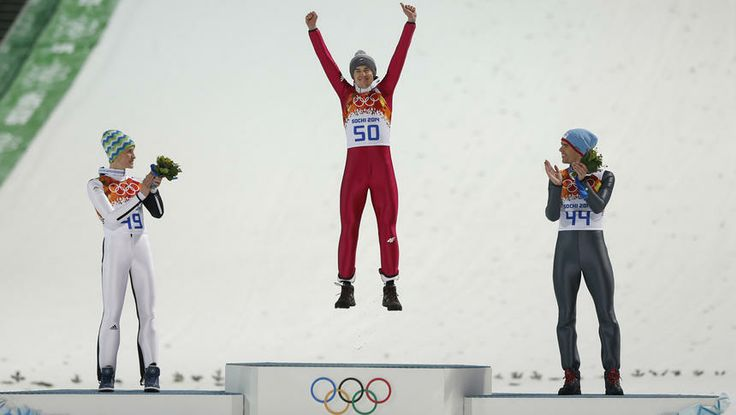 Poland's gold medal winner Kamil Stoch jumps on the podium as he is applauded by Slovenia's silver medal winner Peter Prevc, left, and Norway's bronze medal winner Anders Bardal, right, during the flower ceremony for the men's normal hill ski jumping final at the 2014 Winter Olympics.