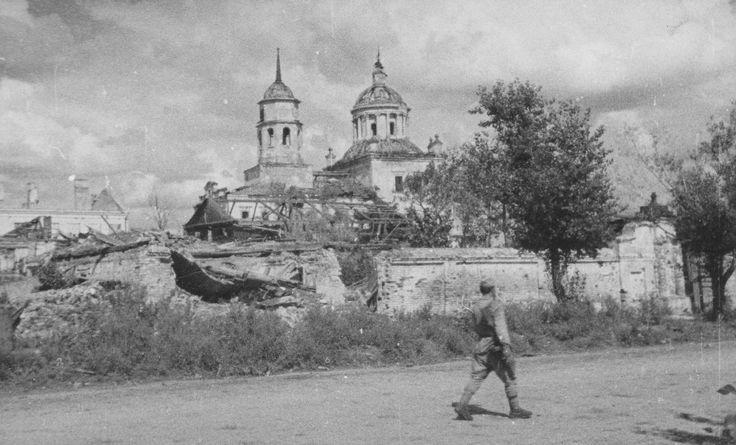 Советский солдат с ППШ проходит мимо Смоленского собора в освобожденном Белгороде. август 1943